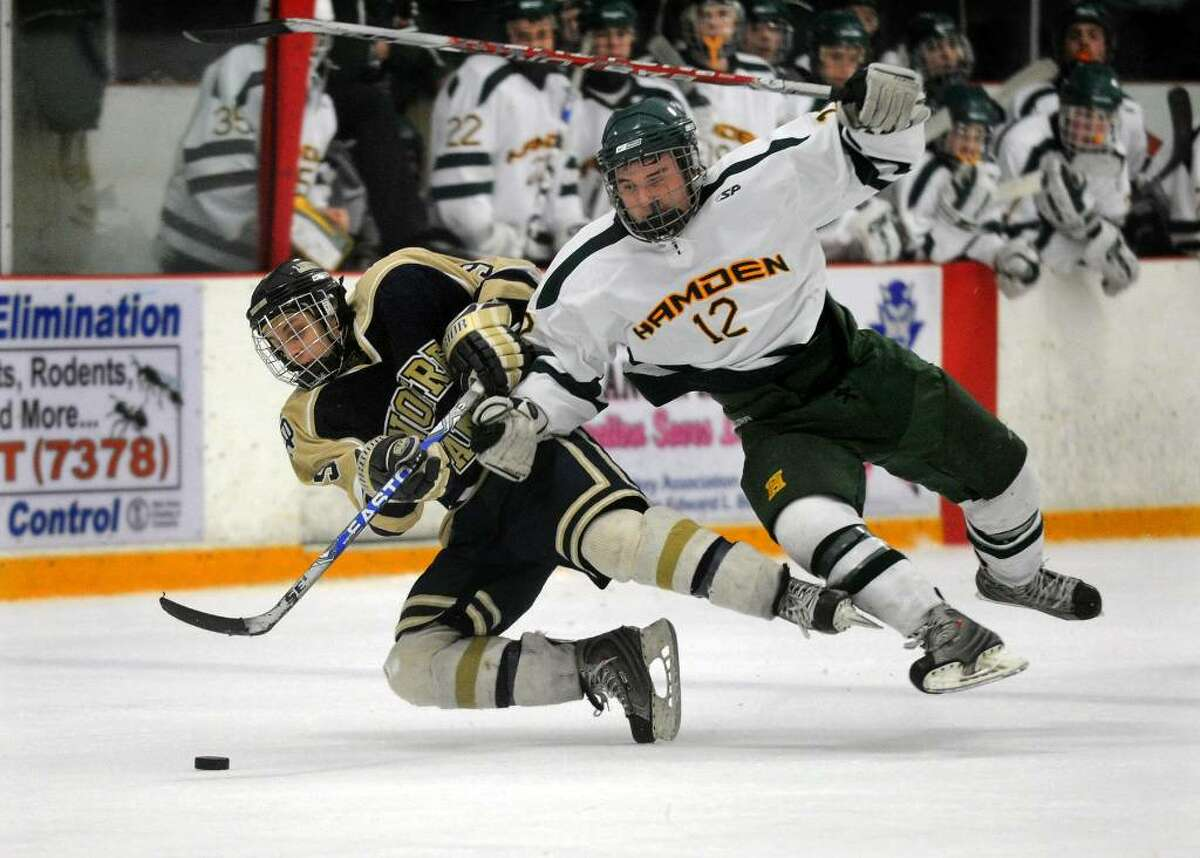 Notre Dame's #9 Brian Sanca, left, and Hamden's #12 Brandon Dadio spill to the ice as they go after the puck, during Division I Quarterfinals in West Haven, Conn. on Saturday Mar. 13, 2010.