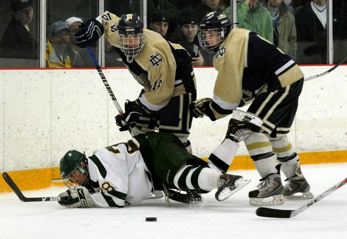 Notre Dame's #16 Steven Novak, left, and teammate #9 Brian Sanca work to get around Hamden's #28 Robert Ugolik to reach the puck, during Division I Quarterfinals in West Haven, Conn. on Saturday Mar. 13, 2010.