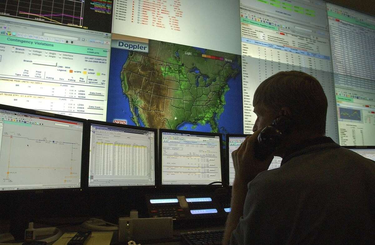 An ERCOT worker mans a desk in the Texas electric grid manager's Austin control room.