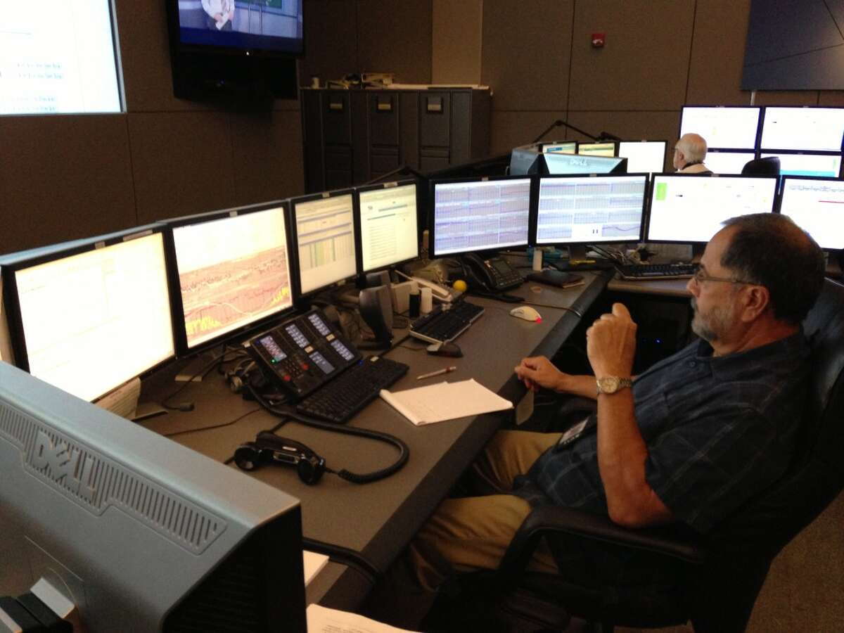 A man monitors information in the ERCOT control center in Taylor, Texas. The Electric Reliability Council of Texas operates much of the state's electric grid from this control center.