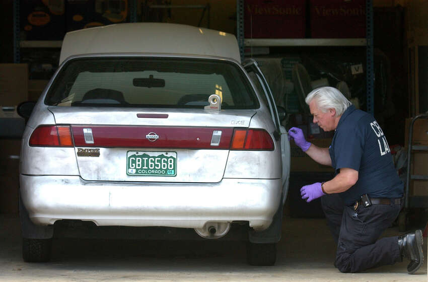 GOLDEN, CO, AUGUST 5, 2003 - Colorado Bureau of Investigation agent Don Sollars checks for fingerprints and other evidence on the 1997 Nissan Sentra that belongs to Heather