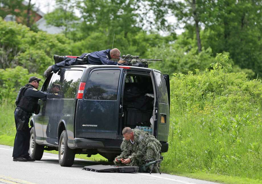 A law enforcement agent looks through a sniper scope while another in camouflage assembles a weapon during a search for two escaped killers in Boquet, N.Y., Tuesday, June 9, 2015.  State and federal law officers are searching for David Sweat and Richard Matt,  two killers who used power tools to break out of Clinton Correctional Facility in Dannnemora, close to the Canadian border.  (AP Photo/Seth Wenig) Photo: Seth Wenig / AP