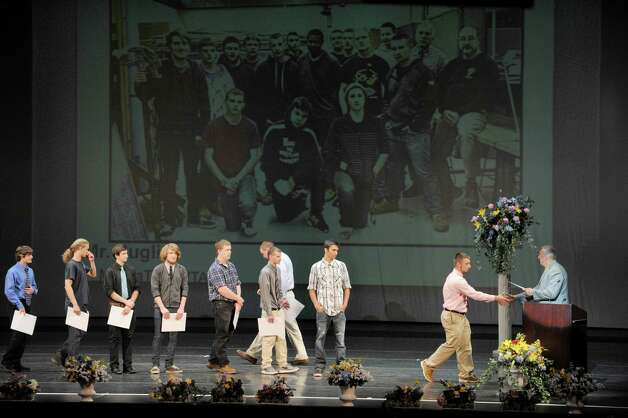 Taylor Russell, far right, a student in the Electrical Trades program, walks up to receive his certificate as students in the Capital Region BOCES program took part in the Capital Region Career and Tech Awards and Recognition Ceremony on Tuesday, June 9, 2015, at Proctors Theater in Schenectady, N.Y.   (Paul Buckowski / Times Union) Photo: PAUL BUCKOWSKI / 00032203A