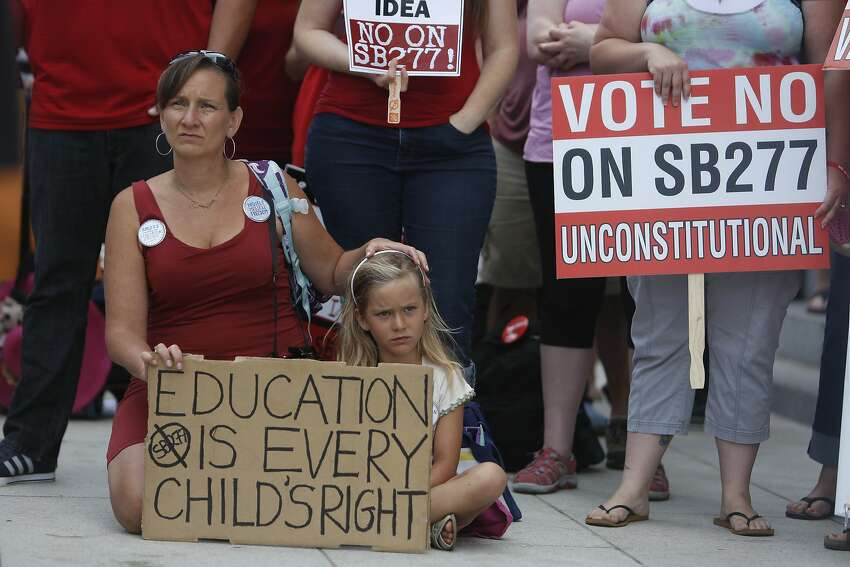 Michelle L'Don-Hayuk (l to r) sits with her daughter Sophia L'Don-Hayuk, 5, both of Brisbane, as they listen to speakers during a rally opposing SB 277 at the Capitol on Tuesday, June 9, 2015 in Sacramento, Calif.