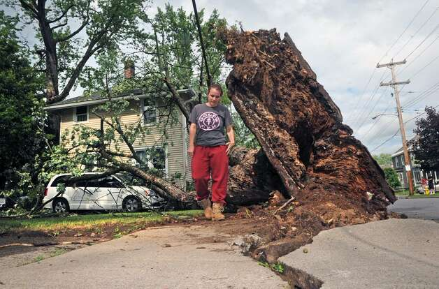 Kristina Mustico  checks out her car which was crushed by an uprooted tree In Scotia on Tuesday. Powerful storms swept through the Capital Region Tuesday afternoon. (Michael P. Farrell)