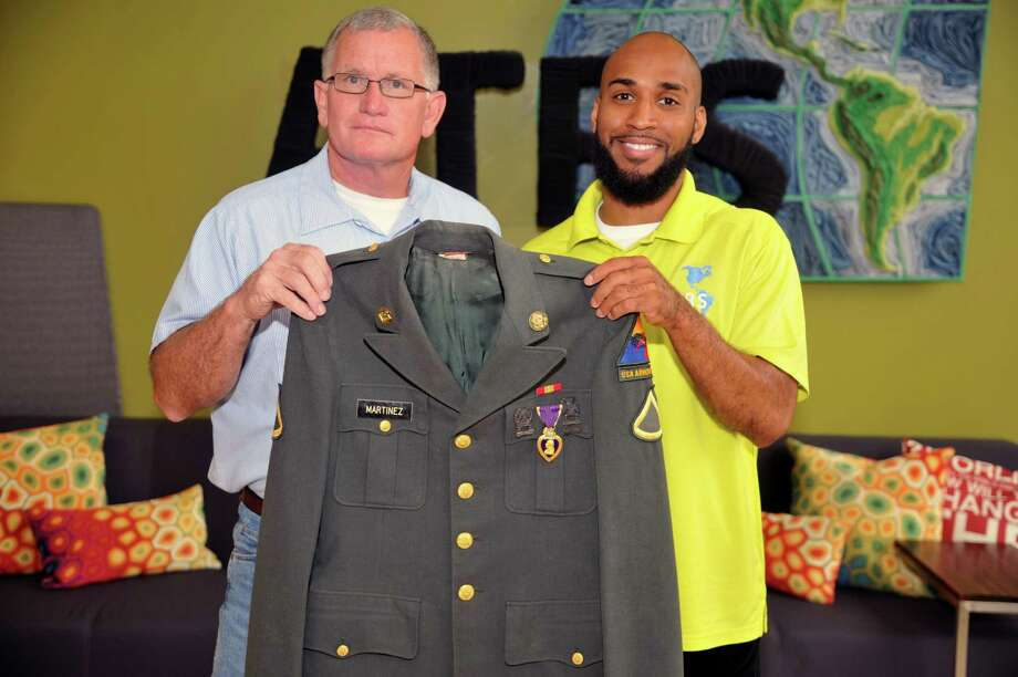 An American Textile Recycling Service employee found a Military jacket with a Purple Heart Medal attached to it.  The jacket was deposited into a recycle bin. Right, Houston Market Team Manager David Taylor stands with fellow employee Charles Andrews, who found the military jacket. 77041, 77395. Photo: Eddy Matchette, Freelance / Freelance