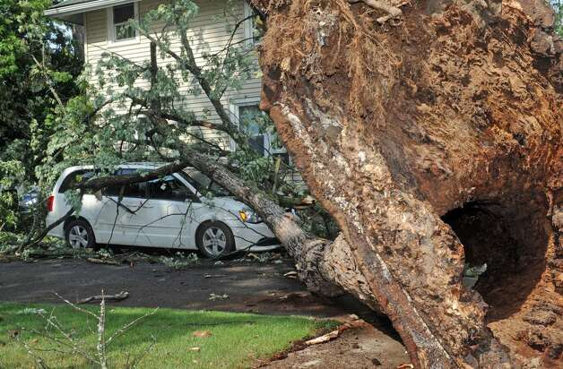 Kristina Mustico  checks out her car crushed by an uprooted tree In Scotia on Tuesday. Powerful storms swept through the Capital Region Tuesday afternoon. (Michael P. Farrell)