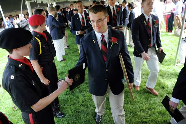 Graduate William Pausley, center, fist bumps a fellow member of the Cadet Corp. after commencement exercises on Tuesday, June 9, 2015, at The Albany Academy in Albany, N.Y. (Cindy Schultz / Times Union) Photo: Cindy Schultz / 00032210A