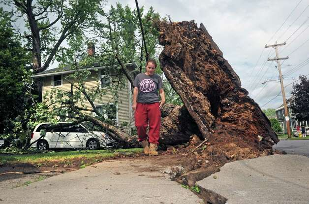 Kristina Mustico checks out the damage to her vehicle and Root Avenue home from a tree uprooted during a passing storm  on Tuesday June 9, 2015 in Scotia , N.Y.  (Michael P. Farrell/Times Union) Photo: Michael P. Farrell