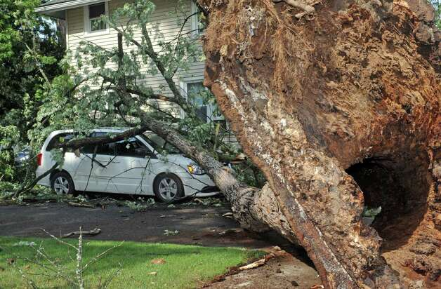 A damaged vehicle in a driveway on Fifth Street and Root Avenue from a tree uprooted during a passing storm  on Tuesday June 9, 2015 in Scotia , N.Y.  (Michael P. Farrell/Times Union) Photo: Michael P. Farrell