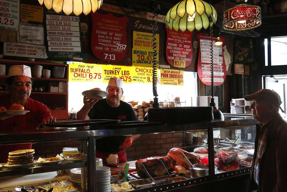 From left, Juan Alvarado and Juan Rubalcaba serve customers lunch, including Carlos Corea, right, at Tommy's Joynt June 9, 2015 in San Francisco, Calif. Photo: Leah Millis, The Chronicle