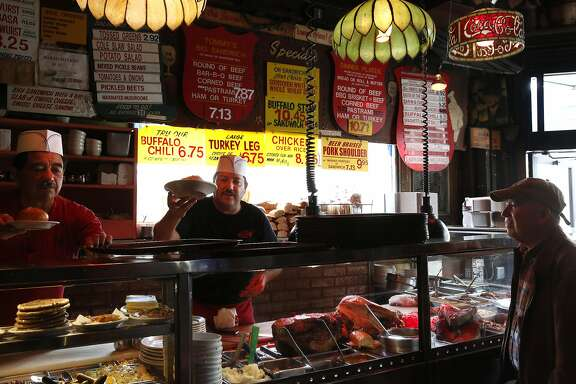 From left, Juan Alvarado and Juan Rubalcaba serve customers lunch, including Carlos Corea, right, at Tommy's Joynt June 9, 2015 in San Francisco, Calif.