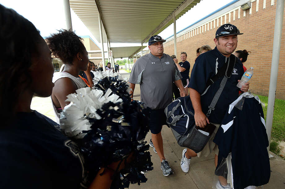 Coach Shea Landry makes his way through a crowd of family, friends and other members of the community, who  turned out Tuesday morning at West Orange Stark High School for a spirited send-off as the Mustangs boarded their bus heading for the baseball state finals. Photo taken Tuesday, June 9, 2015 Kim Brent/The Enterprise Photo: Kim Brent / Beaumont Enterprise