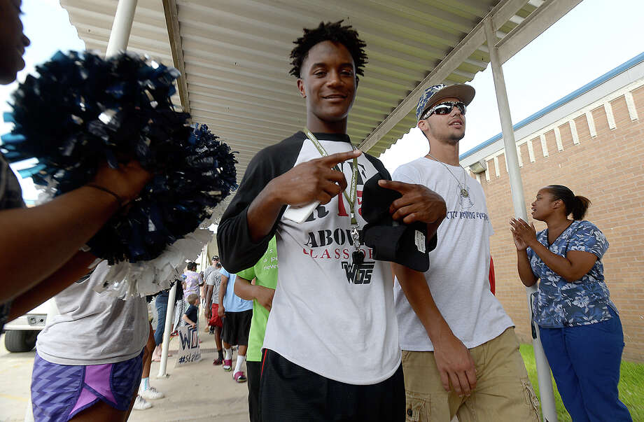 Kalen Garrett (left) and teammates make their way through the tunnel of family, friends and other members of the community who turned out Tuesday morning at West Orange Stark High School for a spirited send-off as the Mustangs boarded their bus heading for the baseball state finals. Photo taken Tuesday, June 9, 2015 Kim Brent/The Enterprise Photo: Kim Brent / Beaumont Enterprise