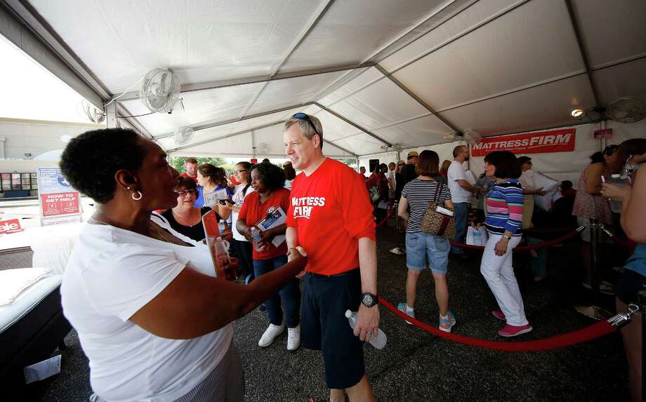 Steve Stagner, right, CEO of Mattress Firm, greets flood victims as they  wait in line during the company's Houston Flood relief program in Meyerland Plaza. Mattress Firm is offering  $700 vouchers for mattresses to flood victims. Photo: Aaron M. Sprecher, FRE / AP Images