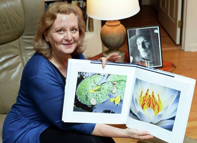 """Eileen Schuyler, widow of the late photographer Joseph Schuyler, with his book, """"Truro Light,"""" published posthumously, at her home Tuesday June 2, 2015 in Delmar, NY. Upper right is a portrait of Joseph Schuyler by John Whipple.  (John Carl D'Annibale / Times Union) Photo: John Carl D'Annibale / 00032095A"""