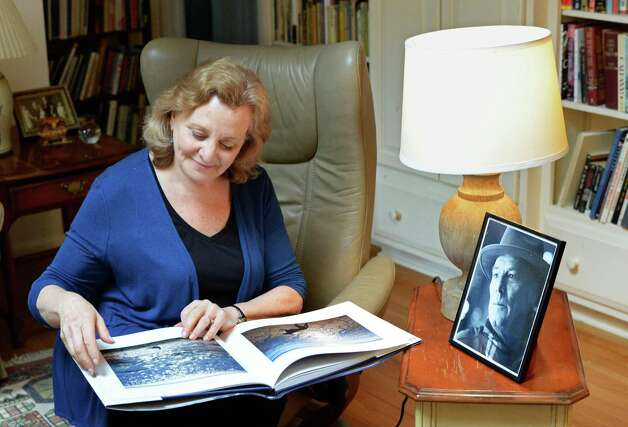 """Eileen Schuyler, widow of the late photographer Joseph Schuyler, with his book, """"Truro Light,"""" published posthumously, at her home Tuesday June 2, 2015 in Delmar, NY. At right is a portrait of Joseph Schuyler by John Whipple.  (John Carl D'Annibale / Times Union) Photo: John Carl D'Annibale / 00032095A"""
