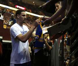 Golden State Warriors' Klay Thompson signs an autograph before playing Cleveland Cavaliers in  Game 3 of the 2015 NBA Finals at Quicken Loans Arena in Cleveland, Ohio, on Tuesday, June 9, 2015.