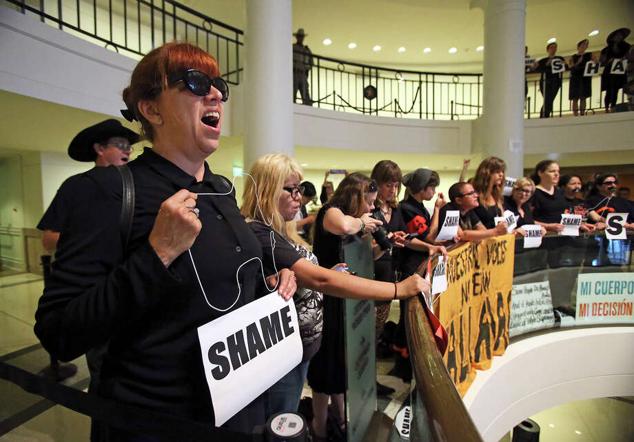Protestors chant holding coat hangers as Governor Rick Perry signs into law the abortions restrictions bill  on July 18, 2013. Photo: TOM REEL