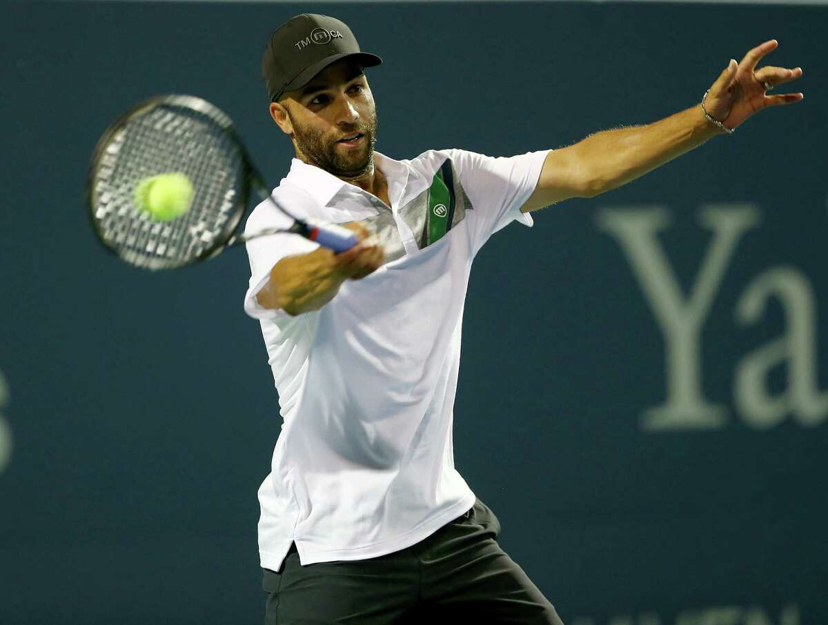 NEW HAVEN, CT - AUGUST 20: James Blake returns a shot to Jim Courier during the Men's Legends match during the Connecticut Open at the Connecticut Tennis Center at Yale on August 20, 2014 in New Haven, Connecticut.Blake defeated Courier 7-5,6-3.