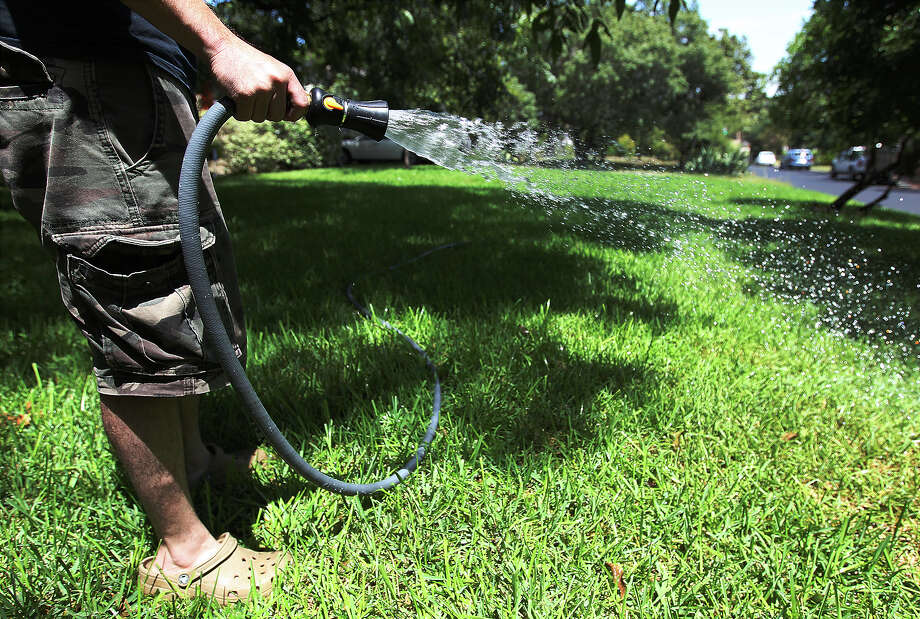 An Alamo Heights resident waters his recently re-sodded yard. A reader says proposed tough water restrictions would be unfair to most area residents. Photo: Kin Man Hui /San Antonio Express-News / ©2013 San Antonio Express-News