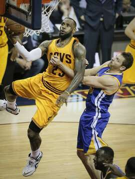 Cleveland Cavaliers' LeBron James drives past Golden State Warriors' David Lee in the second period during Game 3 of The NBA Finals between the Golden State Warriors and Cleveland Cavaliers at The Quicken Loans Arena on Tuesday, June 9, 2015 in Cleveland, Ohio.