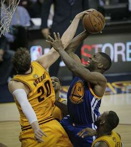 Cleveland Cavaliers' Timofey Mozgov gets a hand on a shot by Golden State Warriors' Festus Ezeli in the third period during Game 3 of The NBA Finals between the Golden State Warriors and Cleveland Cavaliers at The Quicken Loans Arena on Tuesday, June 9, 2015 in Cleveland, Ohio.