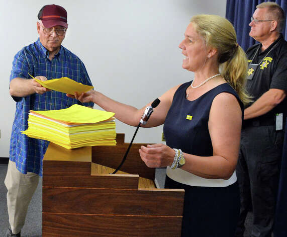Scope attorney Paloma Capanna, center, accepts a FOIL request from John Elms, left, of Binghamton to add to the hundreds they've already collected during a news conference regarding the mental health aspect of the Safe Act at the Legislative Office Building Tuesday June 9, 2015 in Albany, NY.  At right is Fulton County Sheriff Tom Lorey.   (John Carl D'Annibale / Times Union) Photo: John Carl D'Annibale, Albany Times Union / 00032217A