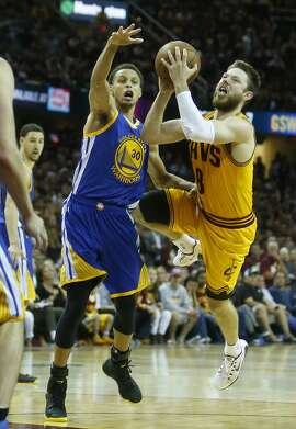 Cleveland Cavaliers' Matt Dellavedova scores and is fouled by Golden State Warriors' Stephen Curry in 4th quarter of Cavs' 96-91 win during  Game 3 of the 2015 NBA Finals at Quicken Loans Arena in Cleveland, Ohio, on Tuesday, June 9, 2015.