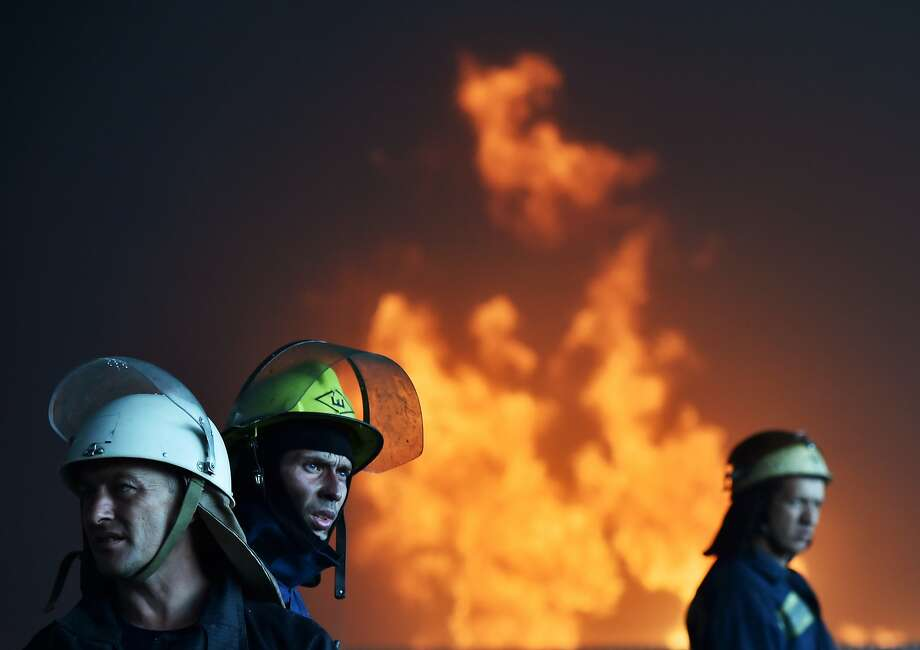 Ukrainian firefighters work to extinguish a fire at a fuel depot in the village of Kryachki, some 30 km southwest from Kiev, on June 9, 2015. Ukraine urgently evacuated hundreds of residents on June 9 from the site of a series of fuel depot blasts near Kiev that set off a ferocious fire and left several people missing and at least one confirmed dead. The defence ministry said it was also taking emergency measures to prevent the flames engulfing a nearby military airbase which has MiG-29 fighter jets and munitions on site. Photo: Sergei Supinsky, AFP / Getty Images