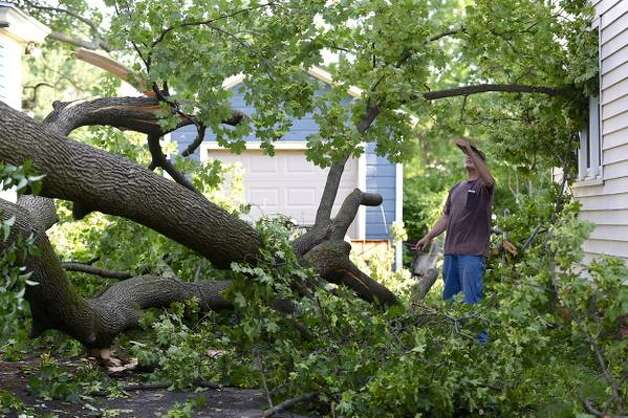 Homeowner Joe Rizzo waits for crane to help remove large tree in his driveway in Scotia on Wednesday morning, a day after a tornado hit the village. (Skip Dickstein / Times Union)