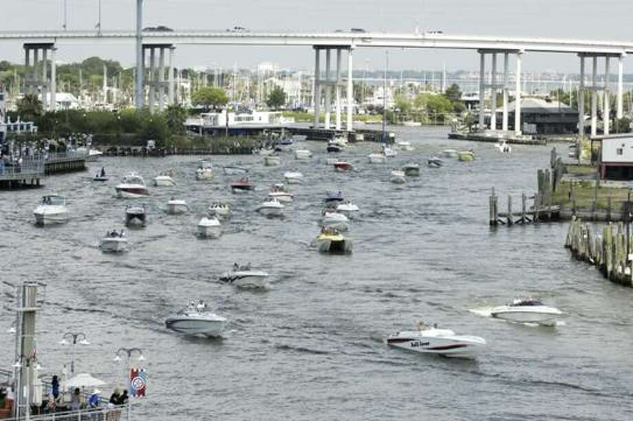 """Boats from a """"poker run""""  in a previous Texas Outlaw Challenge go under the Texas 146 bridge in Kemah. Participants travel to stops where they draw cards, with the best hand winning at the end of the run. Photo: Courtesy"""