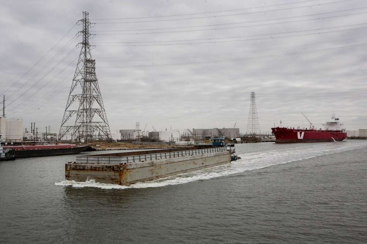 A barge moves along the Houston Ship Channel in Houston, Texas, U.S., on Thursday, Jan. 30, 2014. As record oil and gas output floods the country with cheap and abundant energy and brings the U.S. closer to energy independence, the bulk of the fuels get squeezed through Houston, the country's largest export gateway and the core of its biggest refining region.