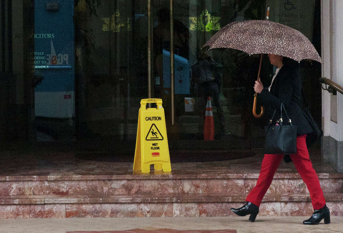 A pedestrian walks in downtown Oakland during a Wednesday morning rain shower.