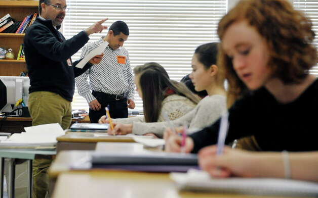 Bethlehem Middle School teacher Jack Rightmyer, left, and Mohammed Belbacha, center, a teacher from Morocco, discuss a poem with students on Tuesday, Feb. 24, 2015, in Bethlehem, N.Y.  The Bethlehem School District was ranked first out of 83 Capital Region schools by a Buffalo business publication.  (Paul Buckowski / Times Union archive) Photo: PAUL BUCKOWSKI / 00030734A