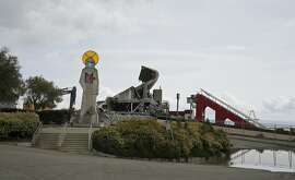 An abstract sculpture representing St. Francis, the patron saint of San Francisco, and a section of stands and escalator ramp still stand as demolition continues at Candlestick Park Thursday, May 14, 2015, in San Francisco. The storied park is being torn down so houses, a hotel and a shopping center can be built on the site of the former home of the San Francisco Giants baseball team and 49ers football team. The park opened more than 50 years ago and was known for its chilly conditions brought by whipping winds and fog from San Francisco Bay. The sculpture, done by Ruth Wakefield Cravath, will be put into storage as city officials seek a new home for it. (AP Photo/Eric Risberg)
