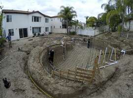 In this photo taken on Wednesday, May 20, 2015, a construction crew digs a new pool behind a house in Tustin, Calif.  As residents struggle to reduce potable water consumption by 25 percent, the California Pool and Spa Association is promoting a campaign called Let's Pool Together and aggressively lobbying water districts to quash proposed bans on filling pools and spas. (AP Photo/Gillian Flaccus)
