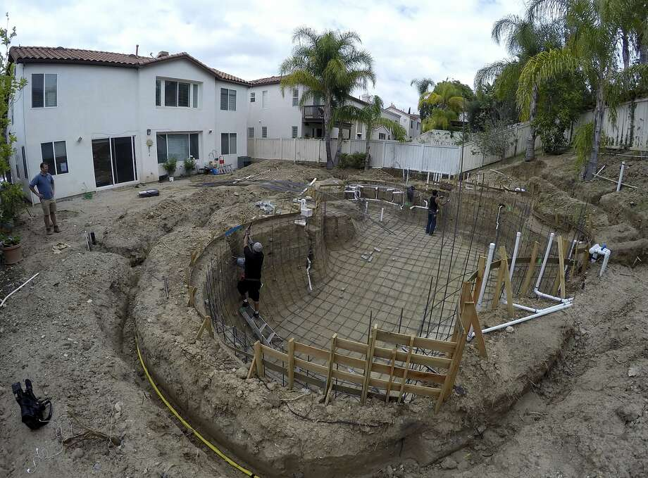 A construction crew digs a new pool in Tustin (Orange County) in May. As residents struggle to reduce water consumption, the California Pool and Spa Association is lobbying water districts to quash proposed bans. Photo: Gillian Flaccus, Associated Press