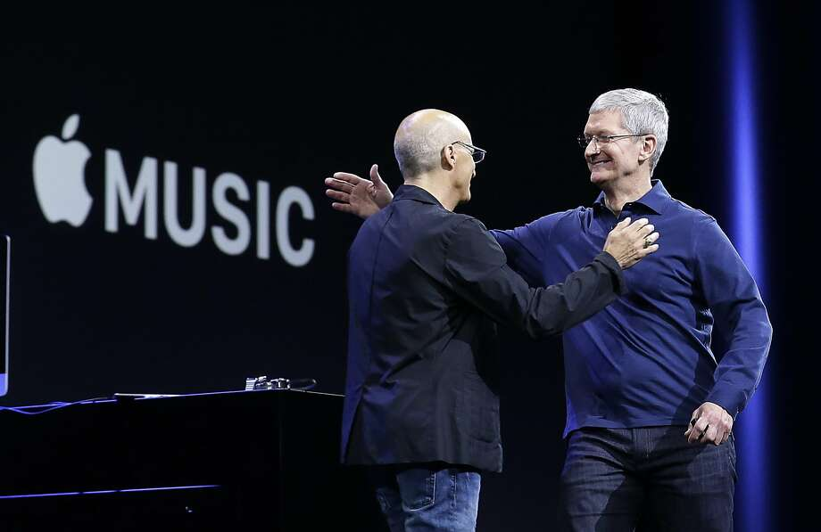 Apple CEO Tim Cook (right) hugs Beats by Dre co-founder Jimmy Iovine at the Monday conference where Apple Music was announced. Photo: Jeff Chiu, Associated Press