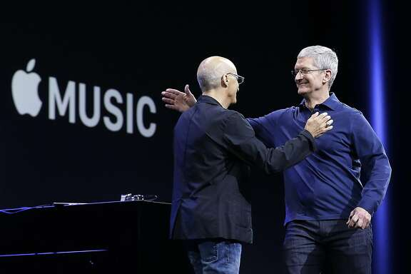 Apple CEO Tim Cook, right, hugs Beats by Dre co-founder and Apple employee Jimmy Iovine at the Apple Worldwide Developers Conference in San Francisco, Monday, June 8, 2015. The maker of iPods and iPhones announced Apple Music, its new, paid streaming-music service to launch this summer. (AP Photo/Jeff Chiu)