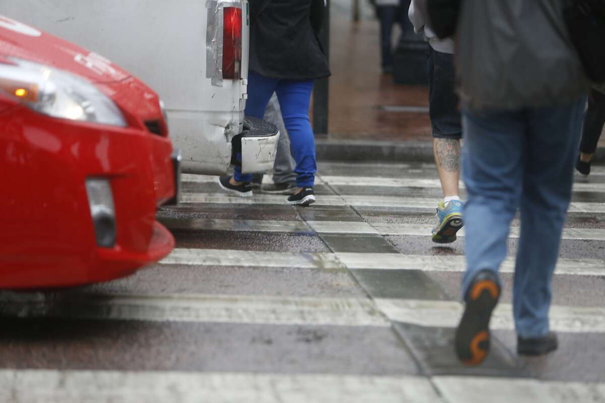 Pedestrians cross in a crosswalk in front of cars that have stopped in the crosswalk on Cyril Magnin Street at Market Street on Wednesday, June 10, 2015 in San Francisco, Calif.