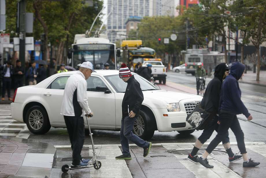 Pedestrians make their way across Market Street  as a car turns from 5th Street onto Market on Wednesday, June 10, 2015 in San Francisco, Calif. Photo: Lea Suzuki, The Chronicle