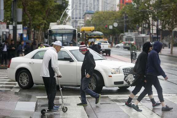 Pedestrians make their way across Market Street  as a car turns from 5th Street onto Market on Wednesday, June 10, 2015 in San Francisco, Calif.