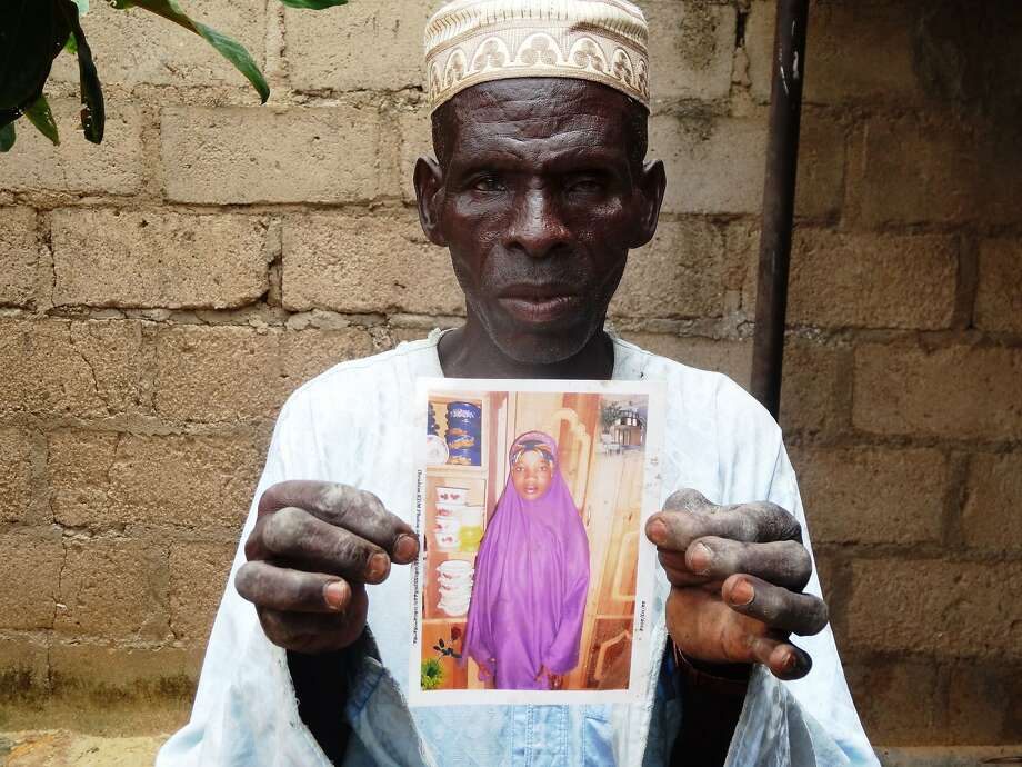 Sani Garba, 55, holds a picture of his then 14-year-old daughter-in-law Wasila Tasi'u inside her abandoned matrimonial home in the village of Unguwar Yansoro, near the northern city of Kano. Nigerian prosecutors withdrew murder charges against a 15-year-old girl who was accused of using rat poison to kill the 35-year-old man she had married. Photo: Aminu Abubakara, AFP / Getty Images