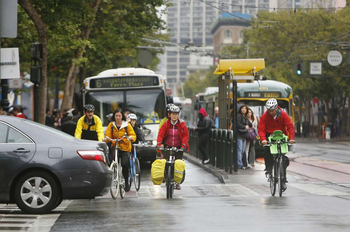 Bicyclists make their way past a car crossing Market Street as they ride in front of buses on Wednesday, June 10, 2015 in San Francisco, Calif.