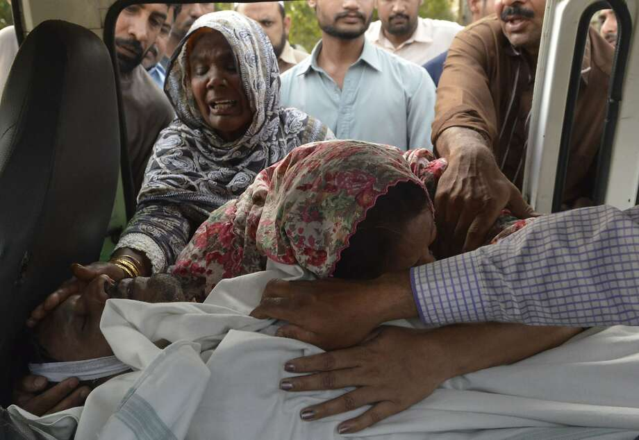 Pakistani Christian relatives of convicted murderer Aftab Bahadur mourn beside his body after his execution in Lahore. Rights activists say he was wrongly executed. Photo: Arif Ali, AFP / Getty Images