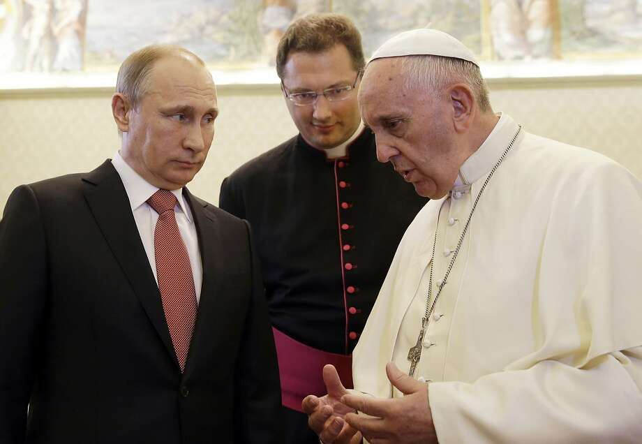 Russian President Vladimir Putin listens to Pope Francis during a private audience at the Vatican. Photo: Gregorio Borgia, AFP / Getty Images