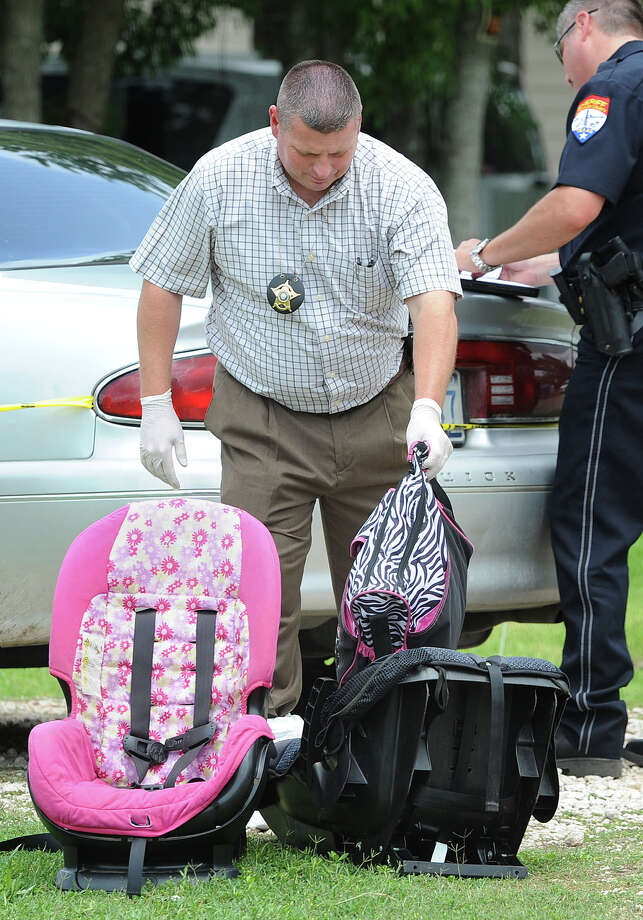 Two child safety seats are collected by deputies during the murder investigation of Tina Gail Aubey in Hamshire on May 23. According to an affidavit, Aubey's twin children were with her when her boyfriend James Martin Chaney asked the 42-year-old woman over and shot her multiple times upon arrival. The children were unharmed and placed with family members. Photo taken Thursday, May 23, 2013 Guiseppe Barranco/The Enterprise Photo: Guiseppe Barranco, STAFF PHOTOGRAPHER / The Beaumont Enterprise