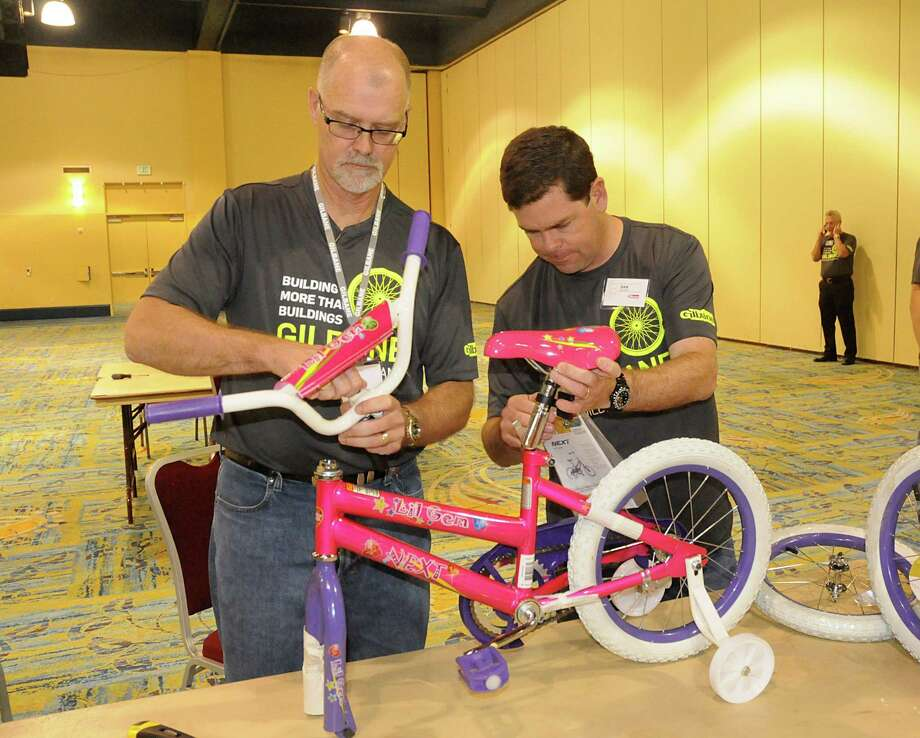 President and C.O.O. Michael McKelvy and Dan Gilbane, Senior VP, put together bicycles during the Gilbane Building Company National Leadership Team's bicycle building project at The Woodlands Waterway Marriott. The Team put together 60 bicycles that will be donated to children through Interfaith of The Woodlands and Montgomery County CASA organization. Photograph by David Hopper. Photo: David Hopper, Freelance / freelance