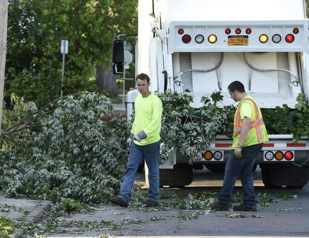 Village employees clean up downed branches in Scotia Wednesday morning, a day after a tornado hit the village. (Skip Dickstein / Times Union)